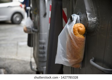 plastic white bag with bread in it, hang on metal container for garbage, left for homeless and hungry people in the city