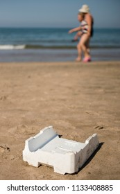 Plastic, white, styrofoam container left on sandy beach with walking people.