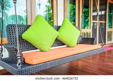 Plastic wicker porch swinging bench with green pillows and orange seat.