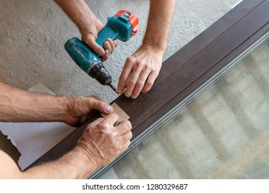 Plastic window frame assembly concept. Two mature laborer man using torque screwdriver assembly energy efficient window frame