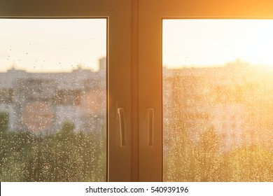 Plastic window with water drops in the sunlight, background