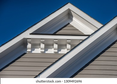 Plastic or wood roof decoration gable, corbel on a new construction luxury American single family home in the East Coast USA with blue sky background