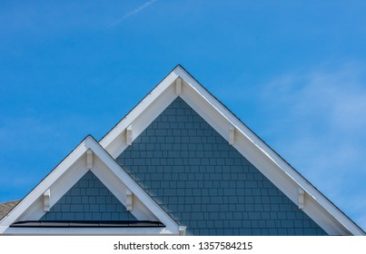 Plastic or wood white roof decoration gable, corbel, louver on a new construction luxury American single family home in the East Coast USA with blue sky background