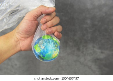 Plastic world or World Environment Day Concept / Hand holds the planet earth in a plastic bag ban say no plastic pollution zero waste recycle