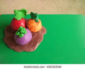 Plasticine clay fruit on green flute board.