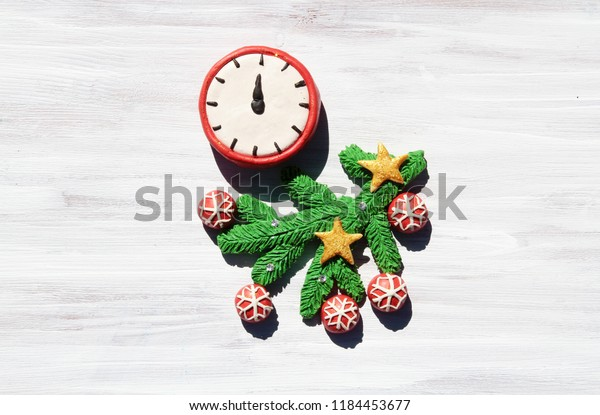 Plasticine clock and a branch of a Christmas tree decorated with red balls ans golden stars on a white wooden background
