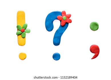Plasticine colored punctuation marks: exclamation mark, question mark, dot, comma with flowers, isolate on white background