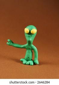 Plasticine figure of alien, on brown
