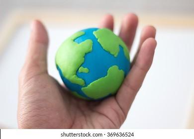Plasticine globe symbolizing the land in the hands , single focus