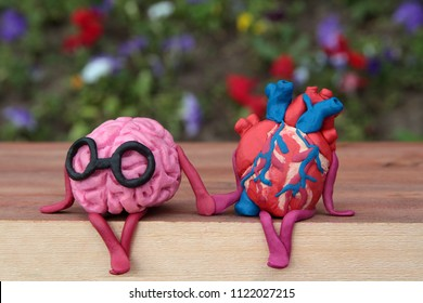 Plasticine human brain and heart are sitting on a wooden bench in the park and holding hands. Happiness, inner peace and harmony concept