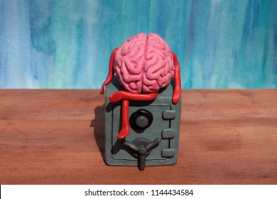 Plasticine human brain is sitting on the safe. Hidden secrets of the subconscious concept