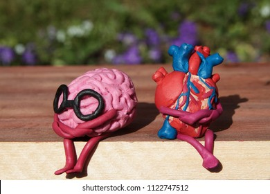 Plasticine human heart and brain are sitting on a wooden bench in the park. Disharmonious unhappy person concept