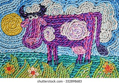 plasticine knitted cow in the meadow