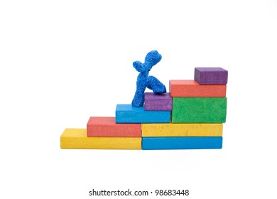 Plasticine man climbing the stairs, made of colorful wooden blocks. The concept of a symbol of hard work, perseverance, commitment to the goal and consistency. Isolated with clipping path on white