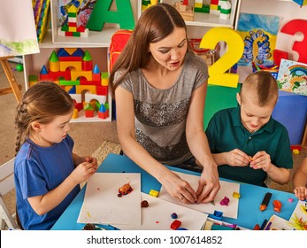 Plasticine modeling clay in children class. Teacher teaches kids together play dough and mold from plasticine in kindergarten or preschool. Educational childhood play room.