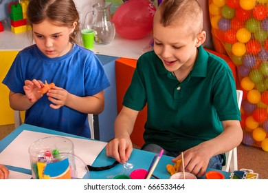 Plasticine modeling clay in children class. Kids together play dough and mold from plasticine in kindergarten or preschool. Group of four people. Teaching modeling. Friendship between boy and girl.