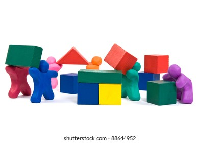 plasticine people working as a team, building wooden blocks