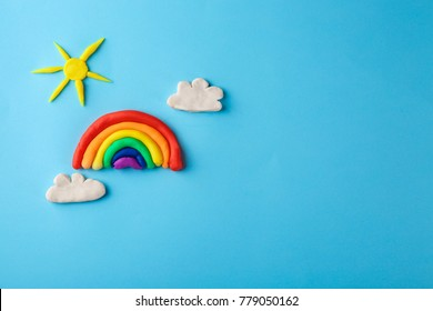 Plasticine rainbow, sun and clouds on color background