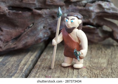 Plasticine world - a caveman with a spear and a stone ax, selective focus