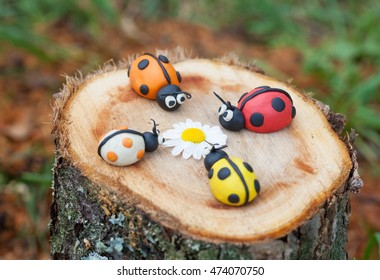 Plasticine world - four little homemade colorful ladybirds sitting on a tree stump, selective focus on red and orange bugs