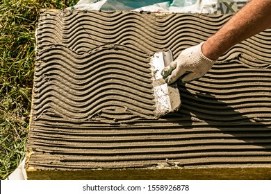 Plastrerer man putting wet thermal glue mortar on rock wool slab (mineral wool, mineral cotton). Insulation installing process. Fiberglass plates for saving house heating energy. Hand with spatula