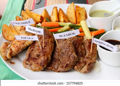 A plate of African game meats with sauces, vegetables, and potato fries.  Meats are marked with little toothpick signs; crocodile, impala, blesbok,springbok