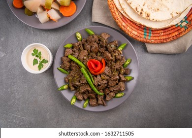 A plate of Alexandria chicken liver, served with tahini sauce white flat bread and pickles.