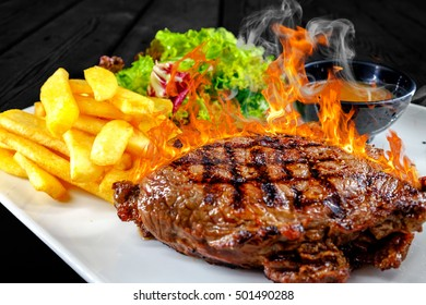 Plate with angus beef steak in flames and smoke. Barbecued meat in fire with potatoes and bowl of red sauce.
