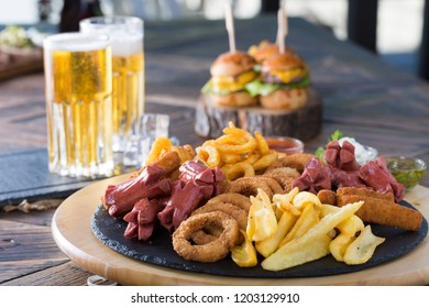 Plate with appetizers for beer; cheese assortment, fried snacks, onion rings, sausages, mustard, french fries, chicken nuggets and sauce.