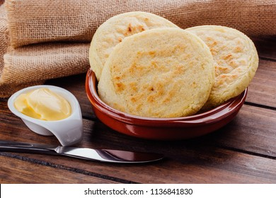 Plate with arepas and butter aside on a rustic wooden background, a typical food in South American countries such as Colombia and Venezuela,
