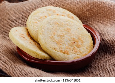 Plate with arepas on a rustic wooden background, a typical food in South American countries such as Colombia and Venezuela,