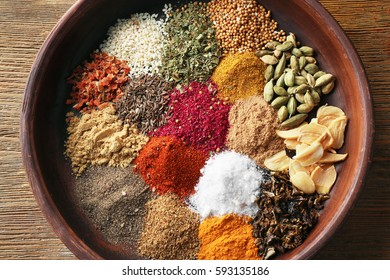 Plate with aromatic spices on wooden background