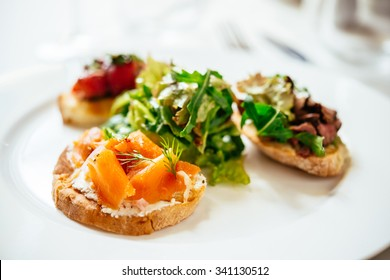 Plate of assorted Italian appetizer bruschetta with chopped vegetables, salmon and meat on ciabatta bread, garnished with green mix salad