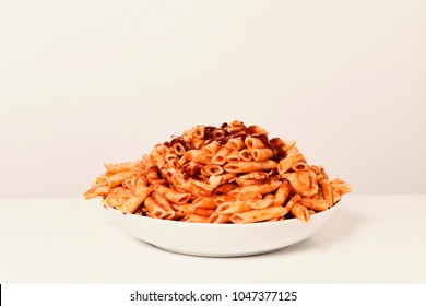 a plate with an assortment of different cooked pasta served with tomato sauce on a white table against a white background, with a blank space on top