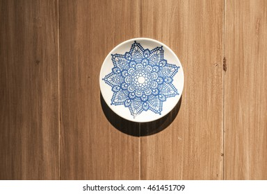 A plate attached to a beautiful pattern is placed on a wooden table as a backdrop to the wall.