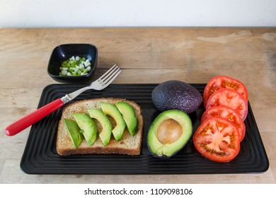 A plate of avocado and tomatoes with green onions on the side and multigrain bread prepared to make avocado toast.