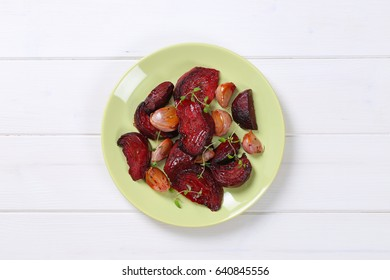 plate of baked beetroot with garlic and thyme on white wooden background