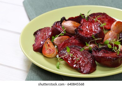 plate of baked beetroot with garlic and thyme on grey place mat - close up