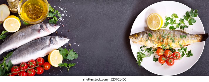 plate of baked sea bass and fresh fish with ingredients for cooking on dark background, top view with copy space.