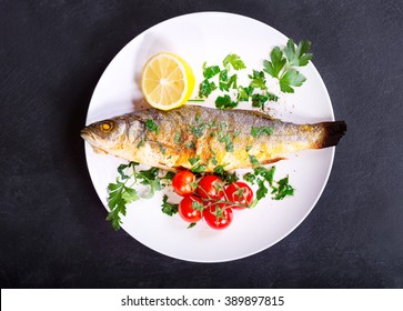 plate of baked sea bass on dark background