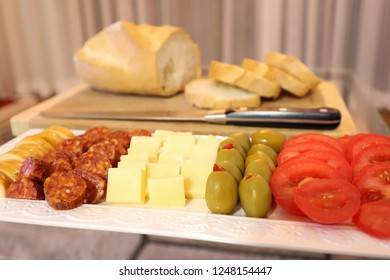 Plate of beautifully arranged apero bites with sliced bread in the background.