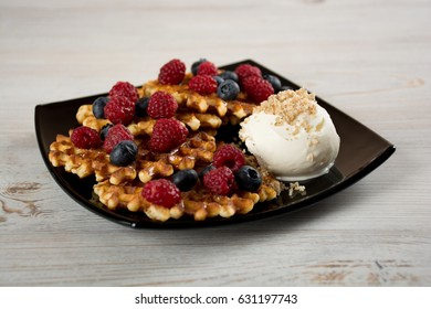 Plate of belgian waffles with fresh berries, ice cream and honey