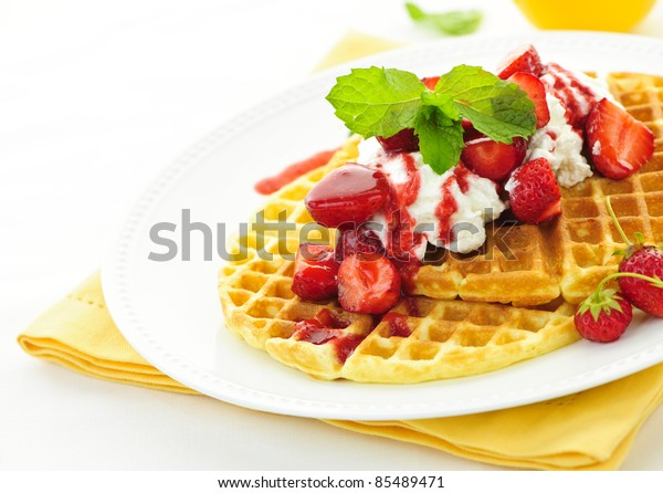 Plate of belgian waffles with fresh strawberries and whipped cream