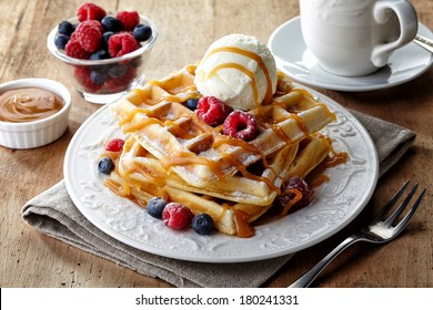 Plate of belgian waffles with ice cream, caramel sauce and fresh berries
