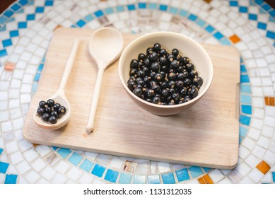 The plate of black currant and a wooden spoon on a wooden tray on a mosaic table. Top view.
