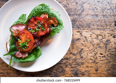 Plate with BLT toast with grilled tomatoes, bacon, lettuce and special sauce on the old wooden table top view