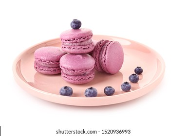 Plate with blueberry macarons on white background