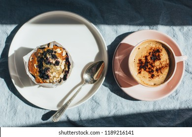 plate of blueberry muffin and cup of coffee