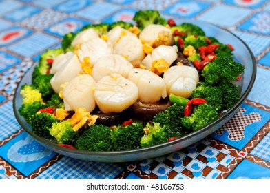 Plate of boiled mushroom and broccoli, topped with scallops
