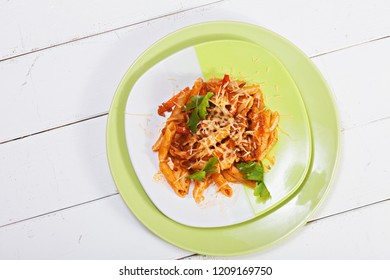 Plate of bolognese pasta over white wooden board. Horizontal overhead shot